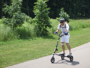 From Randomland: This guy is wearing rubber toe slippers and a brain-bucket on his stand-up tricycle, the operation of which takes up the entire path, which is 3.5 of my giant steps wide. Geez, what spaceship dropped his keester here?