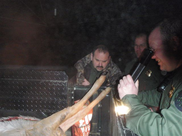CO Mike Mshar's truck in deer season often resembles an abattoir (knacker's yard). Here Officers Ivan Perez and Rabbers are checking identity on some waterfowl Mike confiscated. There is also an illegal deer in the bed of the truck.