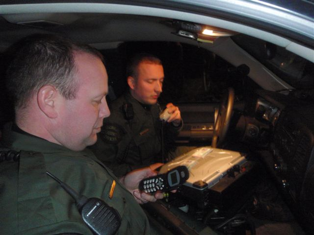 CO Jeff Rabers (left) and Pat McManus confer after making stop in dark in cornfield in Allegan County.