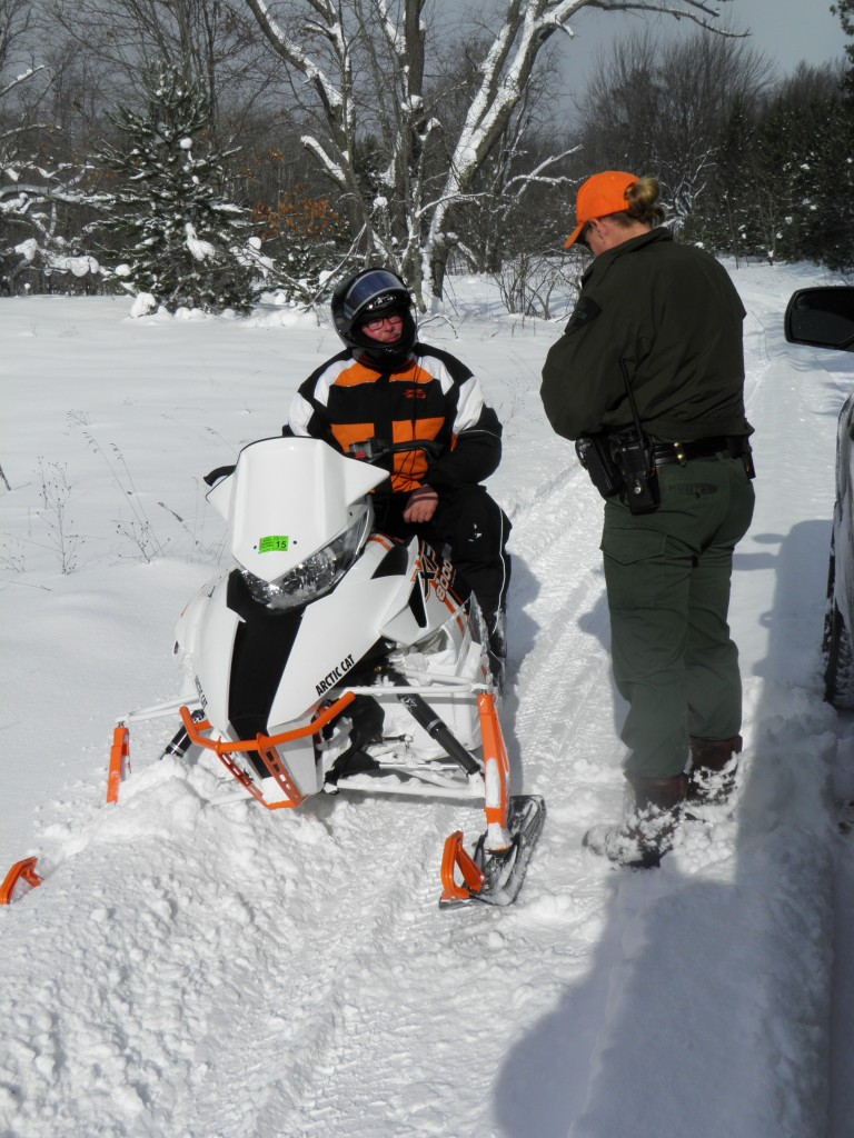 CO Becky Hopkins checking first snowmobiler of the season